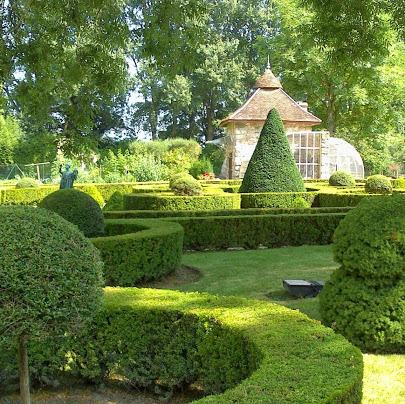 jardin à la française, une création de Paysage Subtil, avec une serre de jardin en arrière plan.